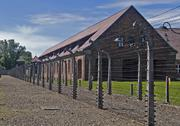 Wire fence and barrack in a uschwitz - birkenau concentration camp Stock Photos