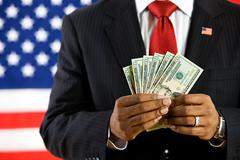 politician: holding a fan of us currency - stock photo