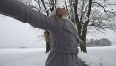 SLOW MOTION: Young woman spinning in winter tree avenue Stock Footage