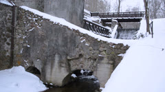 Vintage water mill building creek flow archs stones snow winter Stock Footage