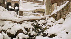 Retro brook dam architecture water flow snow cover stones walls Stock Footage