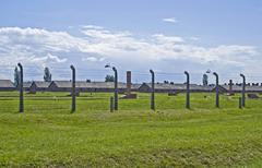 Wire fence and barracks in birkenau concentration camp Stock Photos