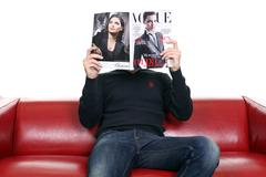 young man with magazine sitting on sofa - stock photo