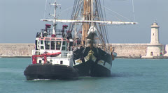 Tugboat towing sailing vessel Stock Footage