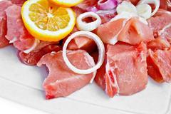 Sliced pork with onion and lemon Stock Photos