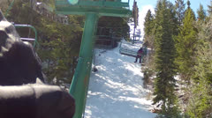 Skiers on chairlift in spring Stock Footage