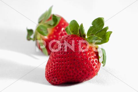 Stock photo of two strawberries isolated on white background
