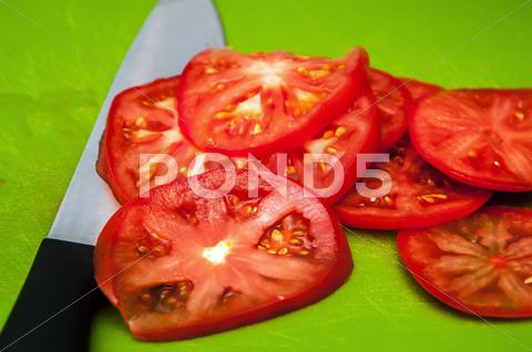 Stock photo of red tomato slices and knife on green chopping board