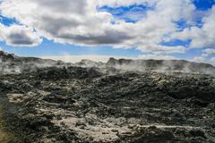 Black lava and steam Stock Photos