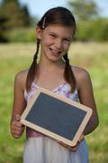 young girl holding a small blackboard - stock photo