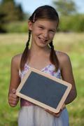 Young girl holding a small blackboard Stock Photos