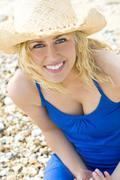 Young girl at the beach in straw hat Stock Photos