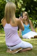 Two young women taking pictures in summer sun Stock Photos