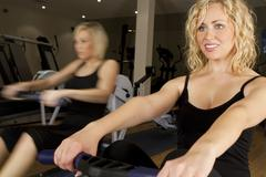 Two young women girls rowing at the gym Stock Photos