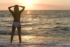 Stock Photo of woman standing in bikini at beach sunset
