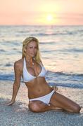 Sexy woman in bikini at beach sunset Stock Photos