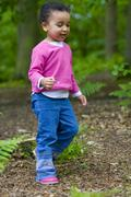 mixed race girl child walking through the woods - stock photo