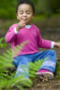 Young mixed race girl playing outside with a flower Stock Photos