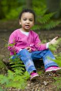 Young mixed raced girl playing with daisy Stock Photos