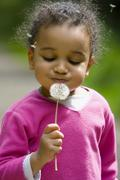 young mixed race girl child playing with a dandelion - stock photo