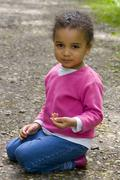 young mixed race girl kneeling down playing - stock photo