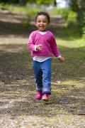 mixed race young girl walking through the woods - stock photo