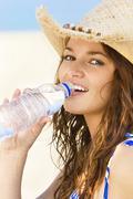 woman drinking water on beach - stock photo