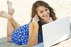 woman on phone and laptop communicating at the beach - stock photo