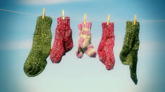 Three pairs of woolen socks hanging on rope Stock Footage
