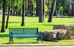 Green bench in tropical park Stock Photos
