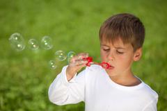 Little boy having fun with bubbles Stock Photos