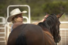 Cowgirl handling horse and riding on horseback Stock Photos