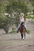 cowgirl handling horse and riding on horseback - stock photo
