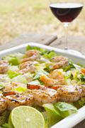Stock Photo of fresh field salad with grilled shrimps, lemon and red wine