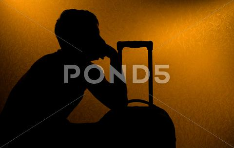 Stock photo of traveling - silhouette of man and suitcase