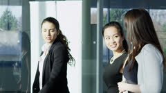 Attractive female business team walking through a modern office building Stock Footage