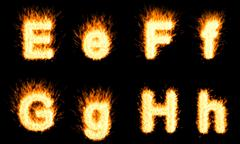 Burning e, f, g, h letters Stock Photos