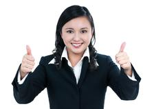 Pretty Asian businesswoman giving two thumbs up gesture - stock photo