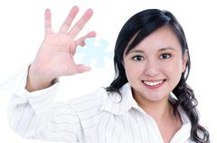 Happy young businesswoman holding jigsaw puzzle Stock Photos