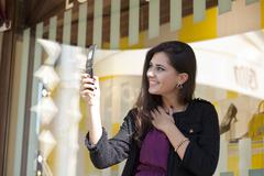 woman posing for a photograph taken from his cell phone - stock photo