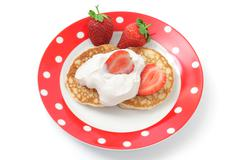 Fritters with sour cream and a strawberry on a plate Stock Photos