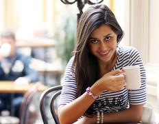 Beautiful young girl sipping coffee Stock Photos