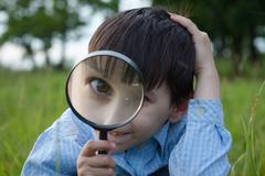Boy with magnifying glass lying on the grass Stock Photos