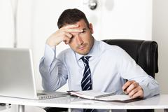 pensive man in office - stock photo