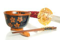 Katana, chopsticks and bowl over white Stock Photos