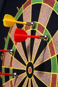Closeup of a dartboard with yellow and red magnetic darts Stock Photos