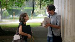 Happy college students talking and laughing in city park Stock Footage