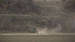 Farmworker Driving Old Tractor in Dusty Field Stock Footage