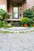 villa backyard with green plant and pebbles - stock photo