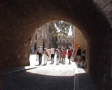 Motorbike and cars driving through stone archway in Rhodes Old Town Stock Footage